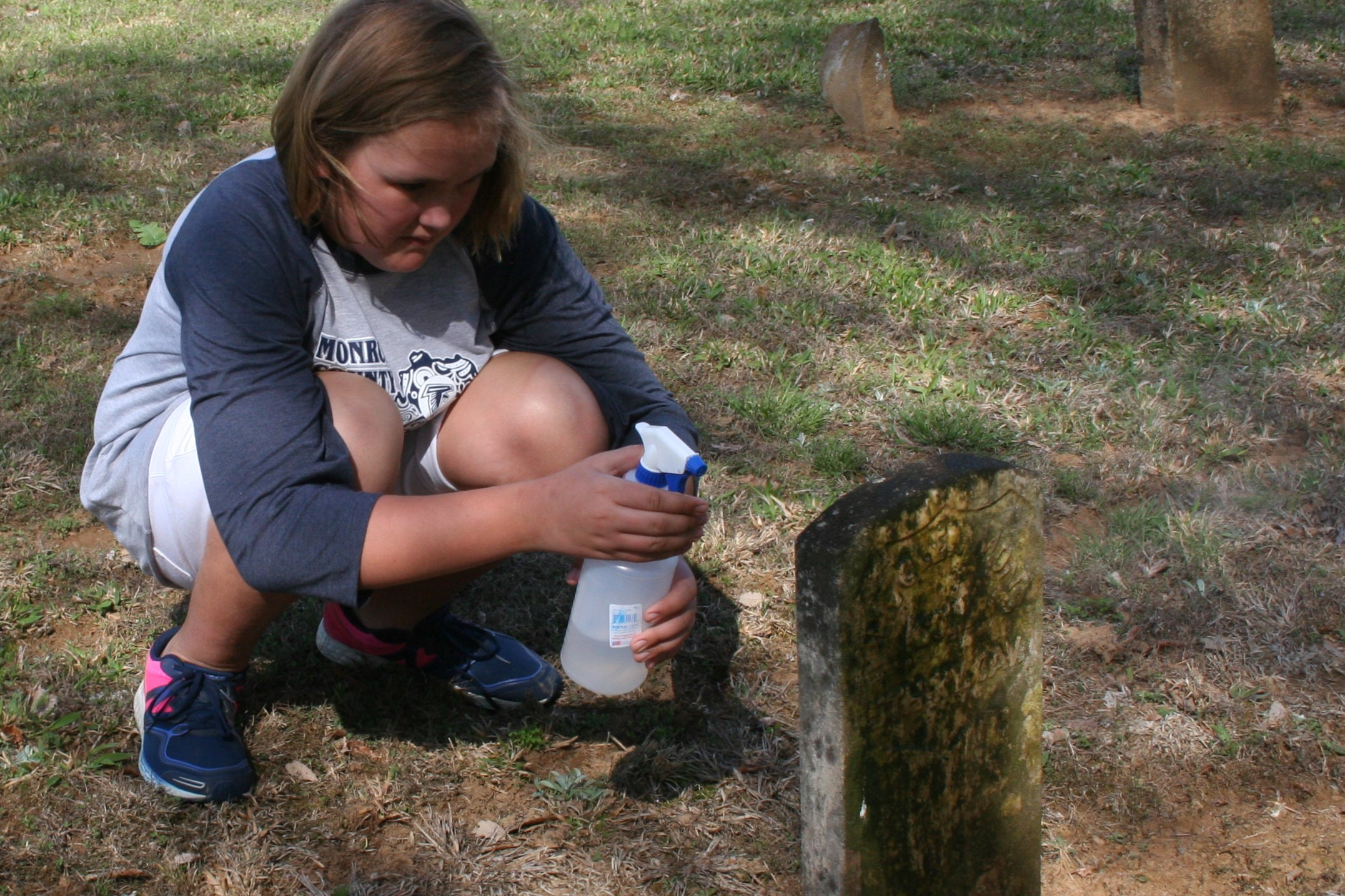 A LImestone member cleans the tombstone of a CIvil War soldier